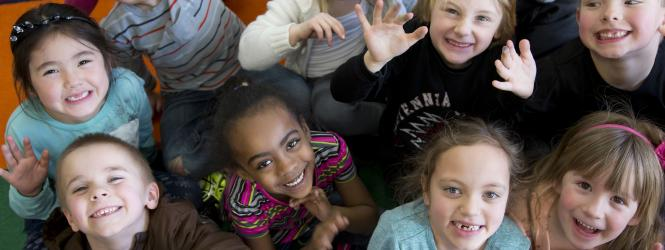 group of elementary aged students looking up and waving at the camera