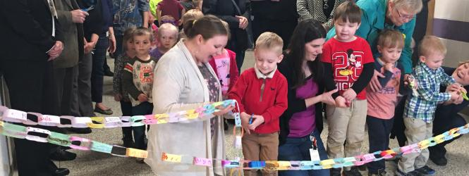 preschool children cutting a paper chain signaling the opening of the new early childhood center