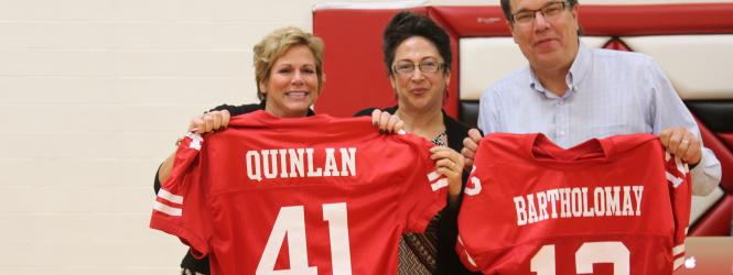 Hall of Fame inductees at pep fest with jerseys. Quinlan's is number 41 and Bartholomay's is number 12.