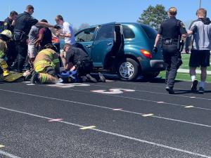 A simulated crash with injured student on the ground and paramedics assisting students