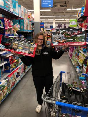 Student holding toys by shopping cart in store