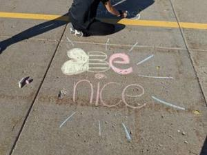Be Kind is written in chalk; the b is a drawing of a bumble bee