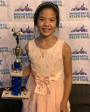 Danica wearing a pink dress with a bow holding her first place trophy and standing in front of a Minnesota State Fair backdrop