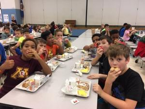 A group of male elementary students sitting at the lunchroom table eating apples and looking at the camera.