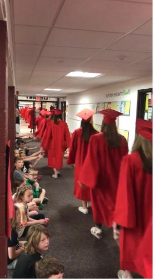 students walking down the hallway of an elementary school in their graduation hats and gowns