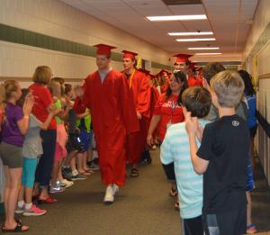 Graduating seniors in caps and gowns walking down the hallway with K-5 students welcoming them.