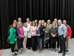 Brian Hegseth with his award surrounded by friends and staff at Centennial