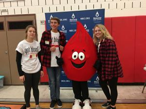 Member of the Senior Class Committee with the Memorial Blood Centers mascot that looks like a drop of blood.