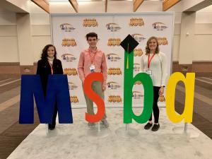 students standing in front of an MSBA backdrop and behind letters--m, s. b, a