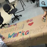 students coloring a large Thank You banner