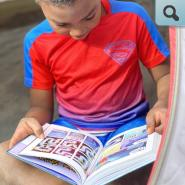 Kindergarten student reading a book at home