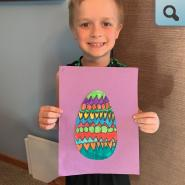 Young student with colored egg art project