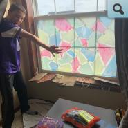 Student standing in front of colorful window