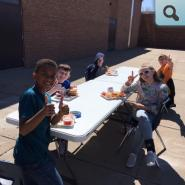 Students eating lunch outside in the sunshine