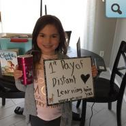 Student holding sign for first day of distance learning