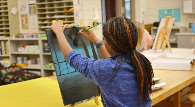a student painting on a canvas