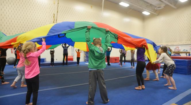 Children playing with a parachute in gymnastics room