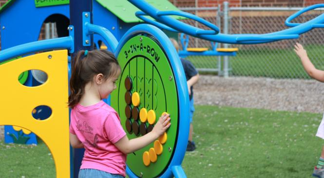 Little girl in pink shirt playing with a 3-in-a-row game on the playground