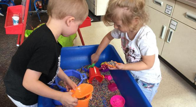 boy and girl using scoops to pick up colored rice in the sensory table